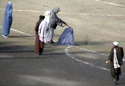 The November 1999 public execution of Zarmeena, a convicted Afghan woman for murdering her husband in cold blood with an ax while he was asleep. The execution was carried out by the Taliban inside the Ghazi stadium in Kabul, Afghanistan. Courtesy Wikicommons.